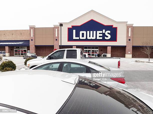 Exterior of a Lowe's home improvement store with vehicles in the parking lot and a sign on the building