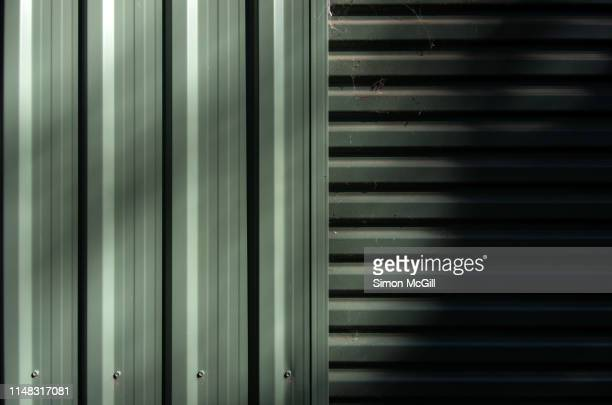exterior of an industrial shed made of khaki green painted ribbed sheet metal - カーキグリーン ストックフォトと画像