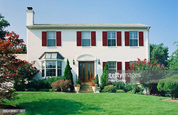 exterior of brick home with crape myrtle and japanese maple - crepe myrtle tree stock pictures, royalty-free photos & images