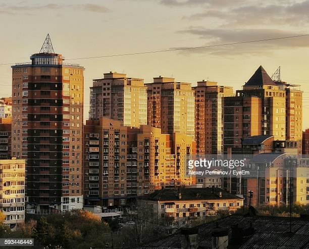 exterior of buildings in city against sky during sunset - khabarovsk stock pictures, royalty-free photos & images