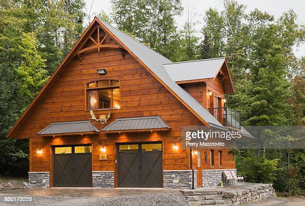 exterior of cottage style eastern white pine log house with double garage - ログハウス ストックフォトと画像