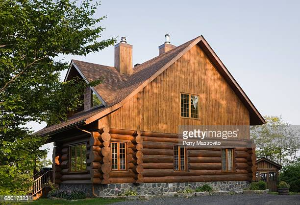 exterior of cottage style log house with cedar shingles - cabaña fotografías e imágenes de stock