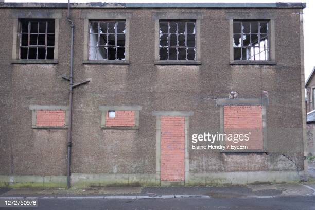 exterior of derelict warehouse with broken windows - abandoned stock pictures, royalty-free photos & images