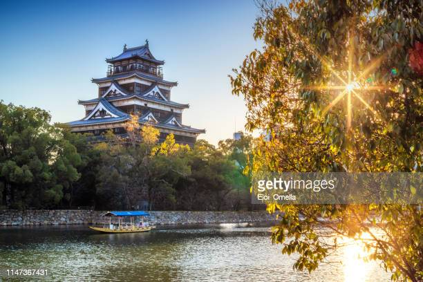 exterior del castillo de hiroshima con turistas barco al atardecer. japón - hiroshima fotografías e imágenes de stock