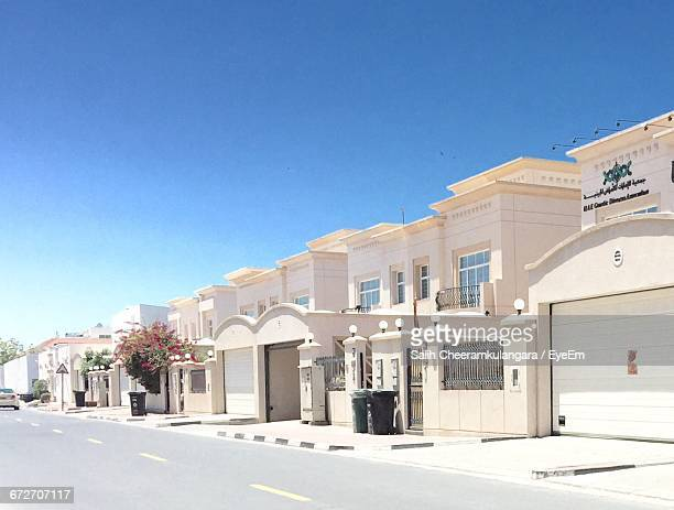 exterior of houses by road against blue sky - facade stock pictures, royalty-free photos & images