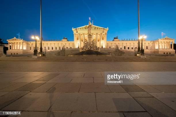 exterior of illuminated austrian parliament building in vienna against clear blue sky at night - wien österreich stock-fotos und bilder