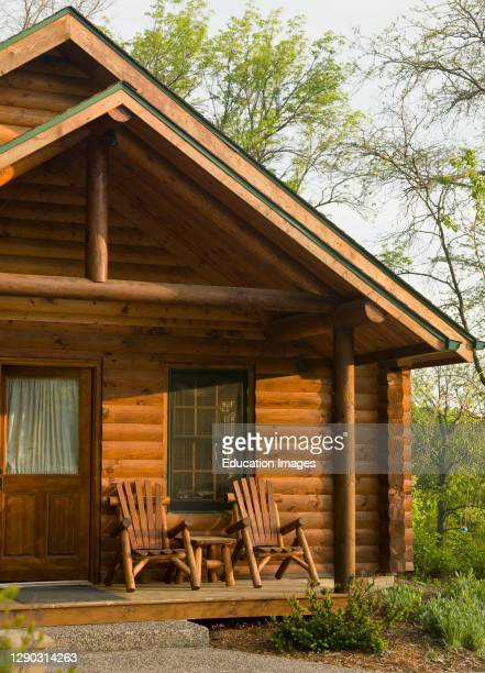 Exterior of log cabin with chairs on porch .