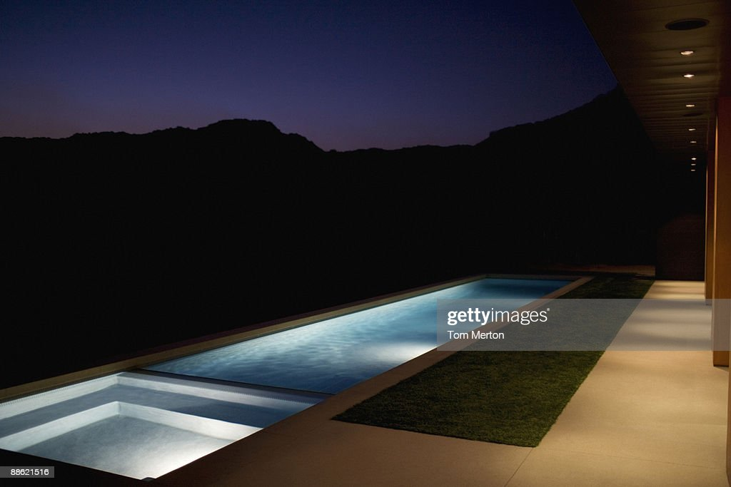 Exterior of modern house and swimming pool at night : Stock Photo