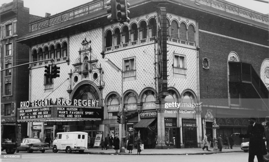 Exterior of RKO Regent Theatre cinema (1912 7th Avenue, at the insection with 116th Street), New York, New York, March 17, 1964. The marquee advertises 'Man's Favorite Sport?' (directed by Howard Hawks), 'Hide and Seek' (directed by Cy Endfield), and 'Dead Ringer' (directed by Paul Henreid).