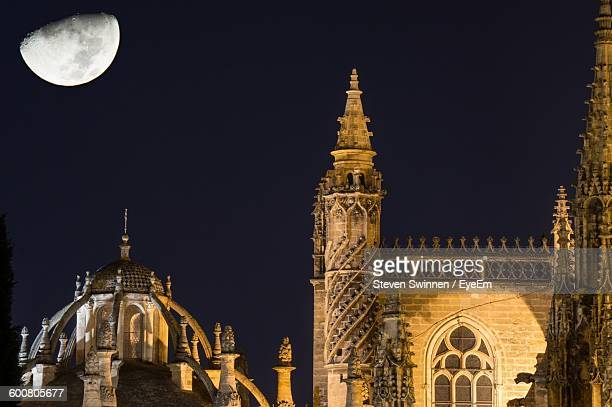 Exterior Of Seville Cathedral Against Moon In Clear Sky At Night