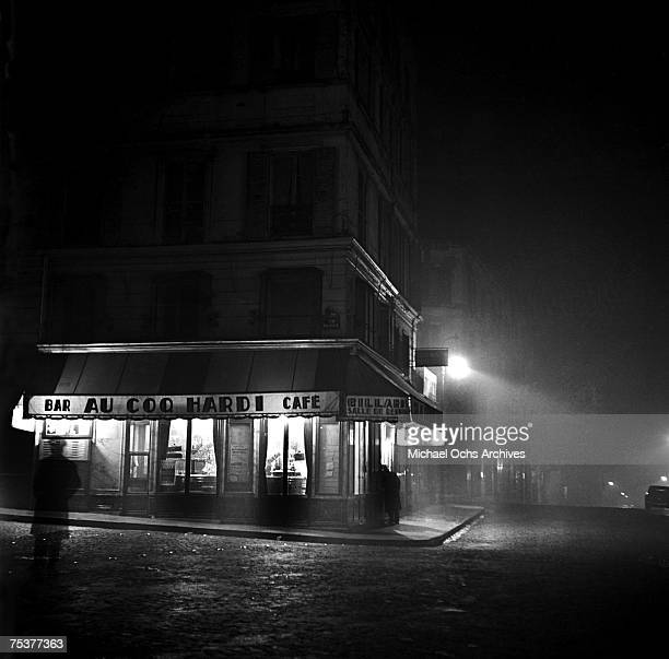 Exterior of the Au Coq Hardi bar and cafe on a foggy street at night on November 1 1948 in Paris France
