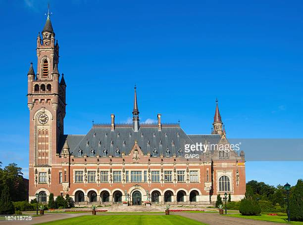 exterior of the hague's peace palace against a blue sky - the hague stock pictures, royalty-free photos & images