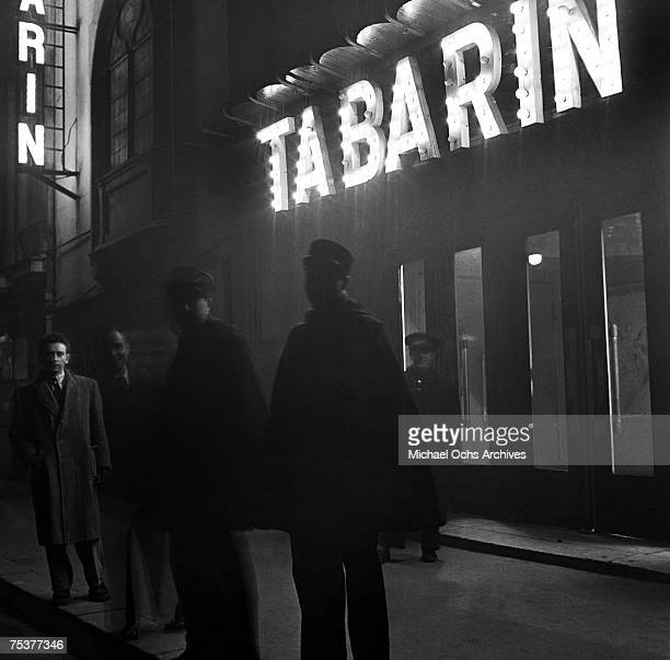 Exterior of the Tabarin nightclub with the doorman and two gendarmes out front on a foggy street at night on November 1 1948 in Paris France