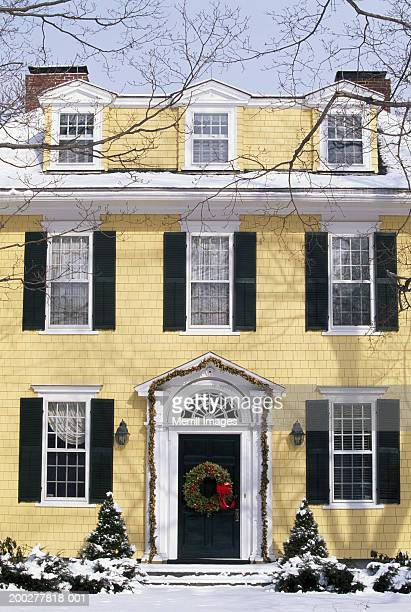 Exterior of yellow house (circa 1907) with Christmas wreath, winter