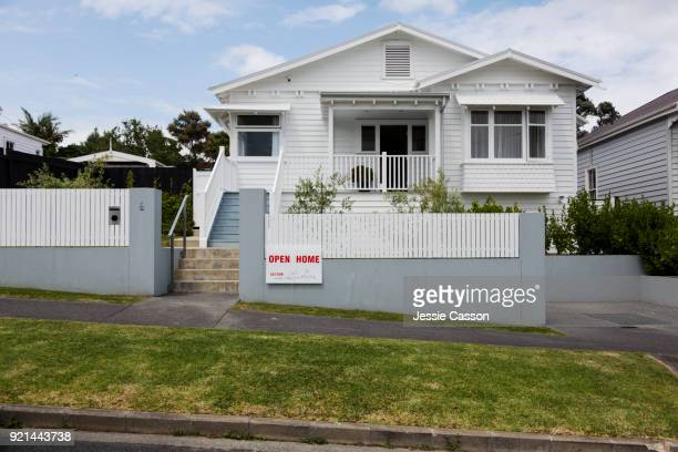 Exterior shot of house with For Sale sign