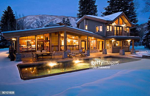 Exterior shot of lit contemporary home in winter.