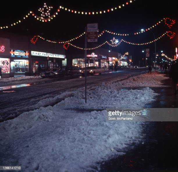Exterior view across a snowy sidewalk of businesses on 63rd Drive in the Rego Park neighborhood Queens New York New York December 1969 Visible are...