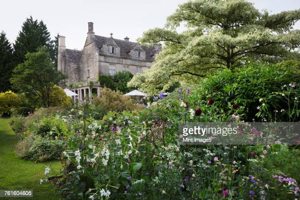 Exterior view of a 17th century country house from a garden with flower beds, shrubs and trees.