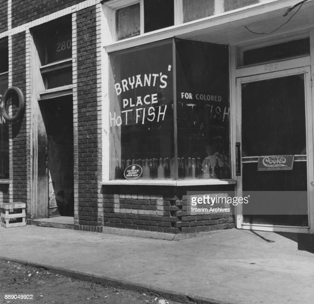 Exterior view of a 'Bryant's Place Hot Fish' sign in a restaurant window Memphis Tennessee June 1937 Another reads 'For Colored'