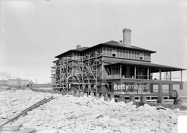 Exterior view of a Chicago Yacht Club boathouse under construction with one side covered in scaffolding and the porch partially finished 1901 The...
