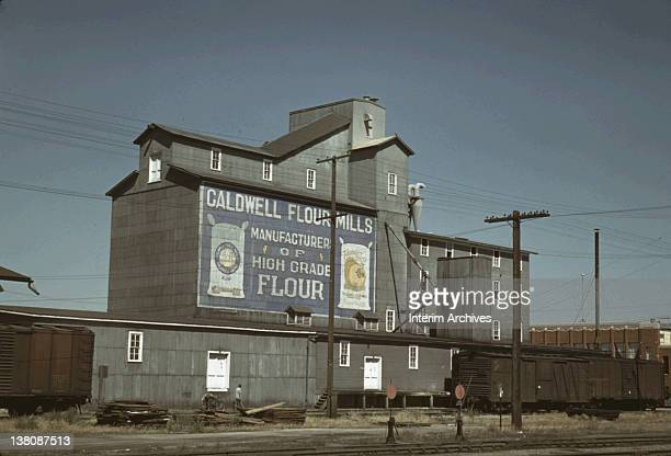 Exterior view of a flour mill in Caldwell, Idaho, July 1941. On the side of the building is painted 'Caldwell Flour Mills Manufacturer Of High Grade...