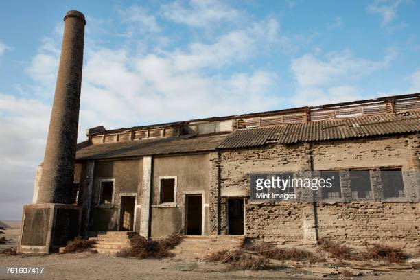 Exterior view of an abandoned building and industrial chimney.