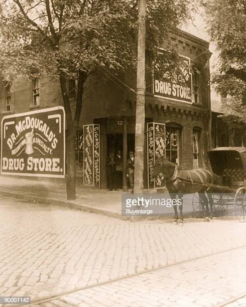 Exterior view of 'Dr McDougal's Drug Store' with three African Americans standing in the doorway and a horsedrawn carriage in the foreground