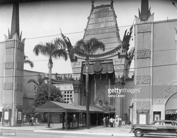 Exterior view of Grauman's Chinese Theater, 6925 Hollywood Boulevard, Los Angeles, California. A couple of people examine the forecourt of the stars,...
