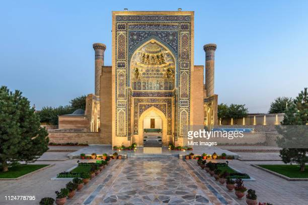 exterior view of historic 15th century madrasa building and courtyard at dusk. - uzbekistan foto e immagini stock
