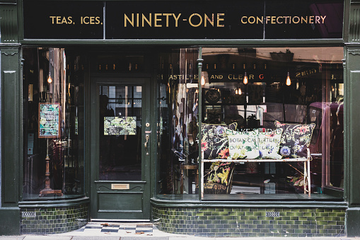 Exterior view of interior design store with floral print cushions on vintage metal bench in shop window. - gettyimageskorea