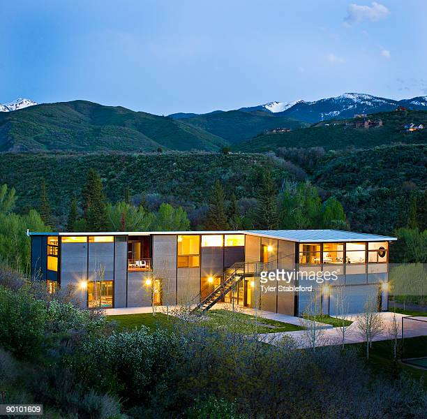Exterior view of lit contemporary house at dusk.