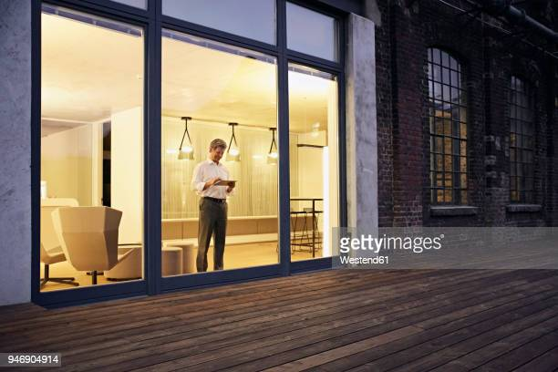 Exterior view of man using tablet in modern building at night