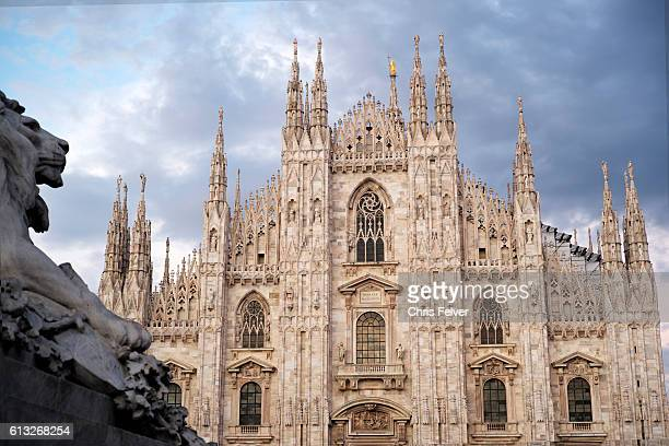 Exterior view of Milan Cathedral Milan Italy May 14 2016 A lion sculpture is partially visible in the foreground