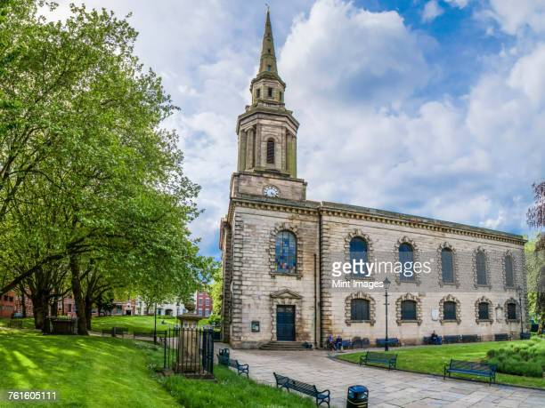 exterior view of st pauls church and tombstones in the churchyard under a cloudy sky. - birmingham uk stock photos and pictures