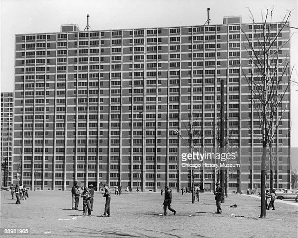 Exterior view of the Cabrini Green housing project with children playing and people miling about in the courtyard Chicago IL ca1960s