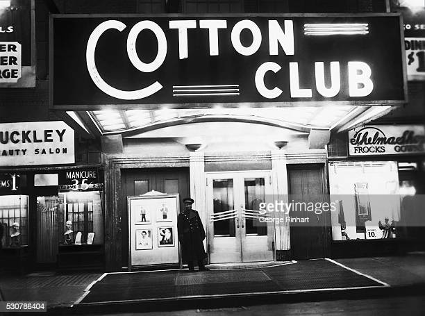 Exterior view of the Cotton Club nightclub where a uniformed doorman stands under the venue's illuminated marquee New York New York late 1930s The...