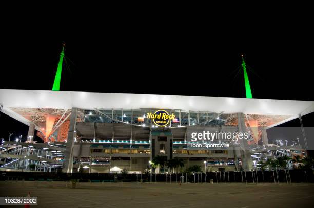 Exterior view of the Hard Rock Stadium lit up with the green and orange colors of the University of Miami after the college football game between the...