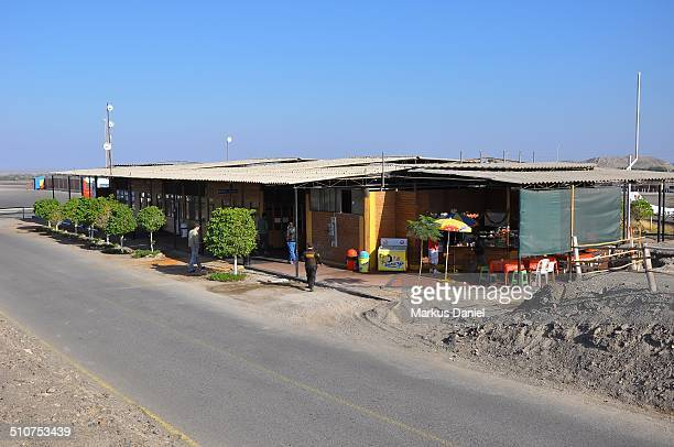 Exterior view of the Nazca Airport Terminal on a clear and sunny day with blue sky with the only access road in the foreground. This is the terminal...