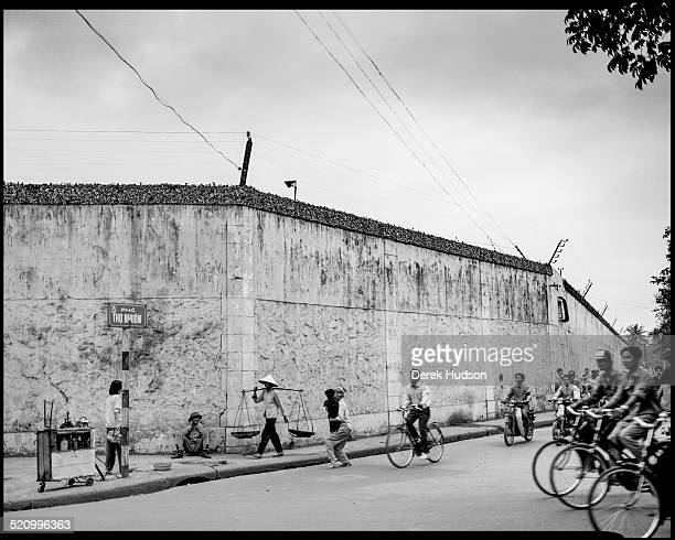 Exterior view of the wall of Hoa Lo Prison nicknamed the Hanoi Hilton as pedestrians and cyclists pass by Hanoi Vietnam 1995 Originally built during...