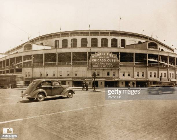 Exterior view of Wrigley Field as cars and pedestrians pass on the street in front of it, Chicago, Illinois, May 1939.