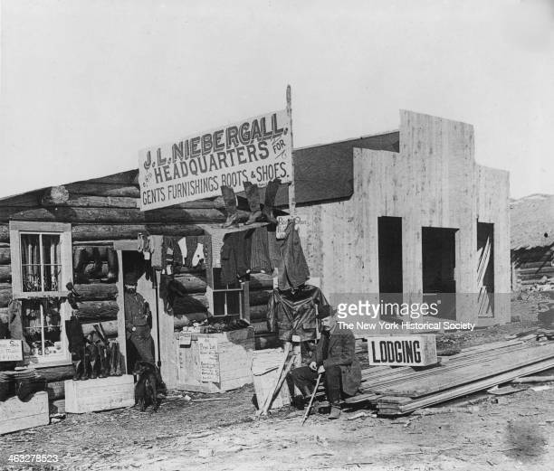 Exterior view with two men visible of JL Niebergall billed as the headquarters for Gents Furnishings Boots Shoes in an unidentified frontier town...