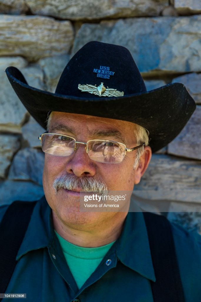 Exterminator with cowboy hat looks for insects and rodents, Oak View, CA : News Photo