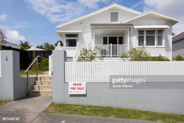 External shot of wooden villa from street with 'For Sale' sign