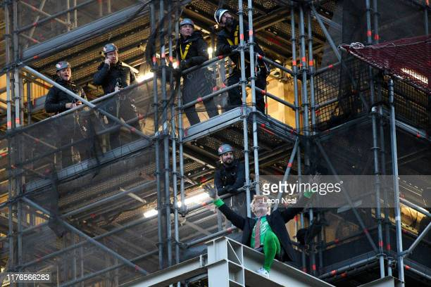 Extinction Rebellion activist Ben Atkinson is watched by police officers after climbing scaffolding on Big Ben at the Houses of Parliament in...