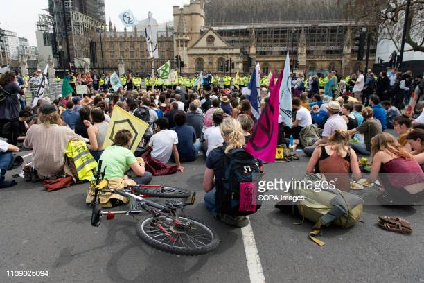 Extinction Rebellion activist sit in the road in Parliament Square during the Extinction Rebellion march in London Extinction Rebellion protesters...