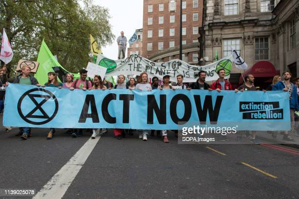 Extinction Rebellion activists are seen behind a large banner marching to Parliament to deliver letters to their MPs during the Extinction Rebellion...