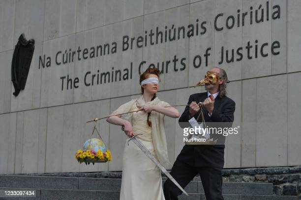 Extinction Rebellion activists, Ceara Carney dresses blindfolded in a gown as Lady Justice and Louis Heath wearing a suit to represent the state seen...