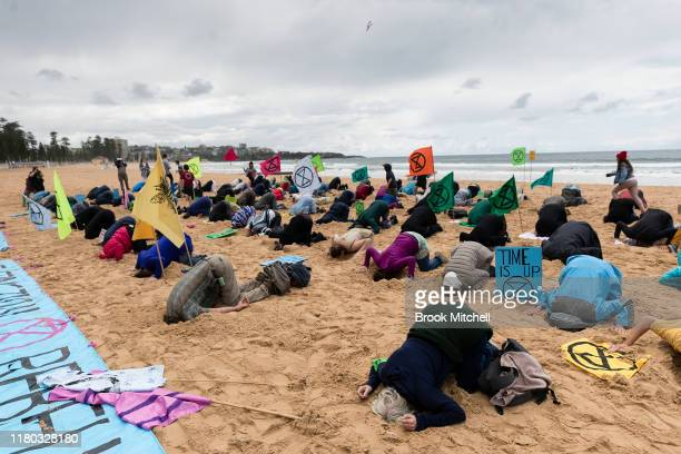 Extinction Rebellion activists gather on Manly beach and bury their heads in the sand on October 11 2019 in Sydney Australia The event was organised...