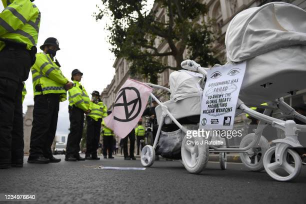 Extinction Rebellion activists stage a demonstration outside Downing Street after a Slow funeral walk with white painted children's prams as part of...
