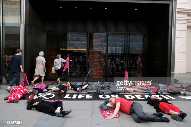 Extinction Rebellion activists staged a diein outside the Royal Opera House main entrance while holding flags during a protest in London...